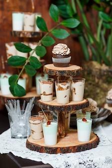 Конфеты-бар на деревянной свадьбе с множеством разных конфет, кексов, суфле и тортов