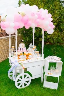 Конфета, шоколадный батончик. белая деревянная тележка со сладостями, украшенная воздушными шарами на зеленой траве