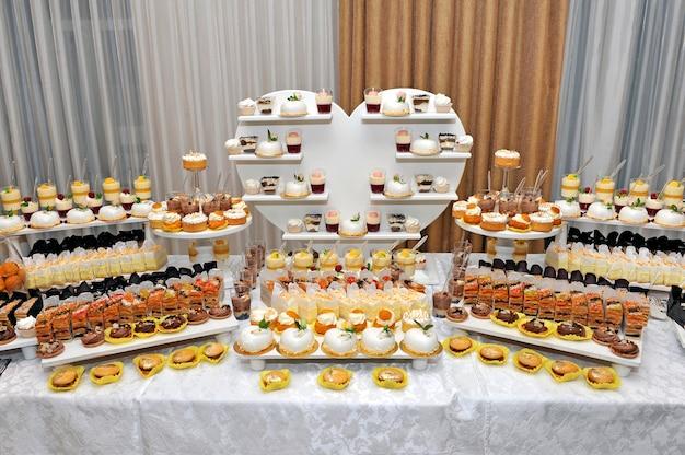 결혼식 기간 동안 쿠키, 칵테일 및 음료와 캔디 바. 파티를위한 디저트 테이블. 결혼식에서 달콤한 테이블.