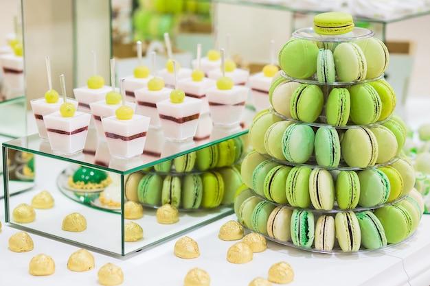 マカロン、ケーキ、チーズケーキ、ポップケーキのあるキャンディバー。カラフルな緑のマカロンピラミッド。