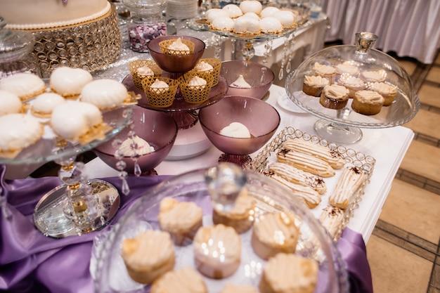 紫色のテーブルにムースデザート、エクレア、パティスリーを備えたキャンディバー