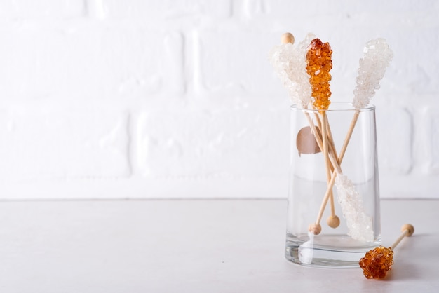 Candy brown and white sugar on a sticks in glass