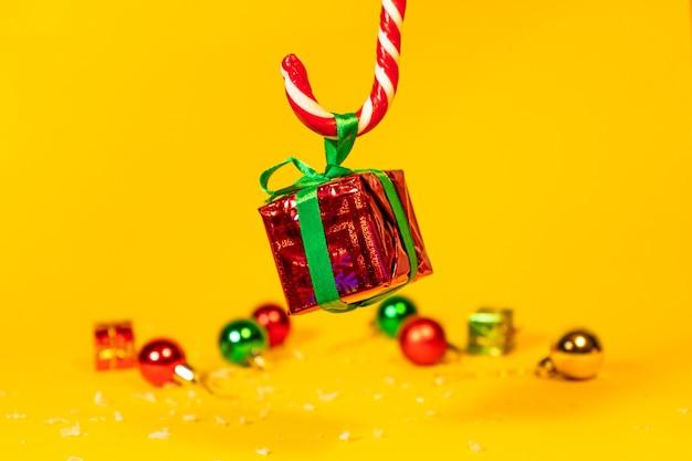黄色の背景にクリスマスプレゼント、新年の装飾が施されたクリスマススイーツのギフトボックスを保持しているキャンディケインロリポップ。