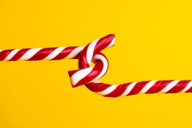 노란색 배경, 크리스마스 과자에 사탕 지팡이 막대 사탕.