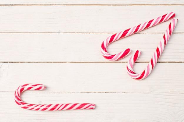 白い木の背景の上のキャンディの杖