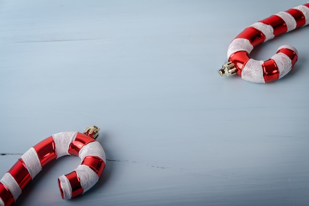 Candy cane shaped christmas toys on a white cracked wooden surface with a copy space