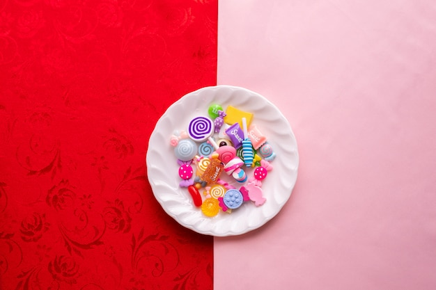 Candy cane on white plate with pink and red tablecloth texture background.