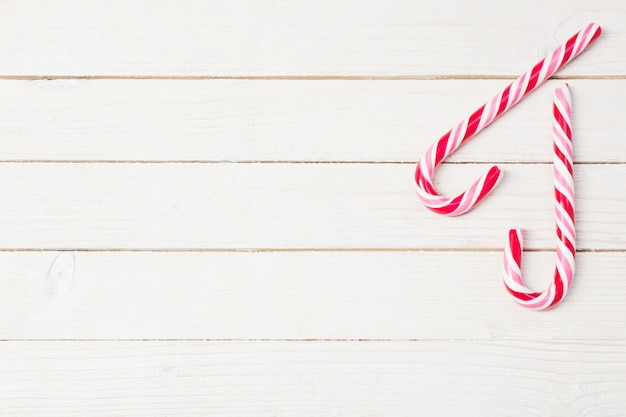 Candy cane on white wooden background