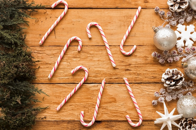 Candy canes between christmas decorations andconiferousbranches