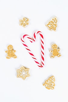 Candy canes and homemade ginger cookies on a white background