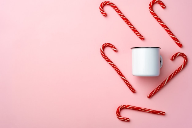 Candy canes on pink background top view flat lay