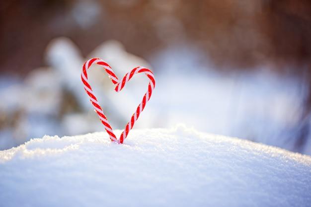 雪の上のハートのような形のキャンディー杖。愛とバレンタインの日の概念。
