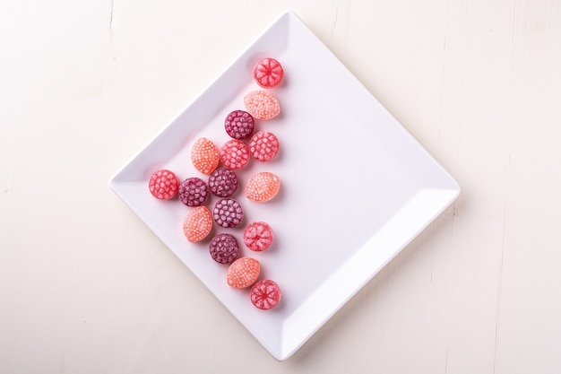 Candy canes sweets in form of juicy berries on white plate on white background isolated, top view