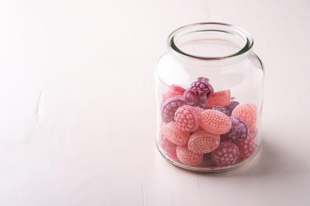分離した白い木製の背景にガラスの瓶にジューシーなベリーの形のキャンディー菓子