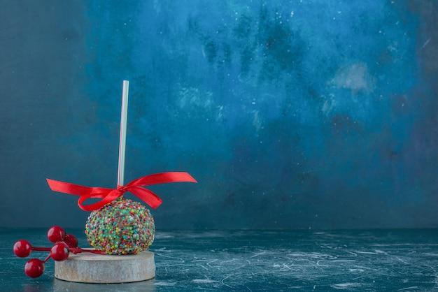 Un lecca-lecca ricoperto di caramelle e un ornamento di bacche di natale su un pezzo di legno su sfondo blu. foto di alta qualità