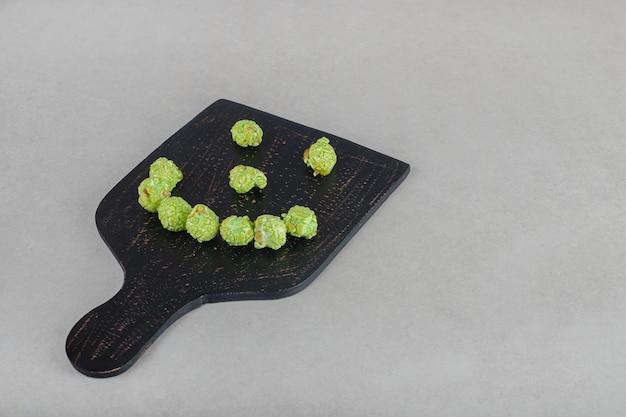 大理石のテーブルの上にある木の板にスマイリーフェイスに配置されたキャンディーコーティングされたポップコーン。