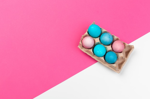 Candy color easter eggs over pink paper background