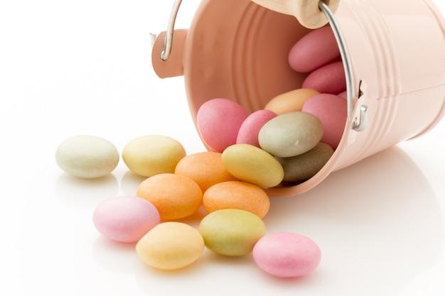 白い背景で隔離のキャンディー色の小さなバケツ。