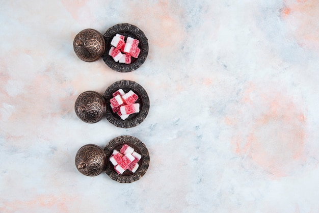 Candy crockery in a row over white surface