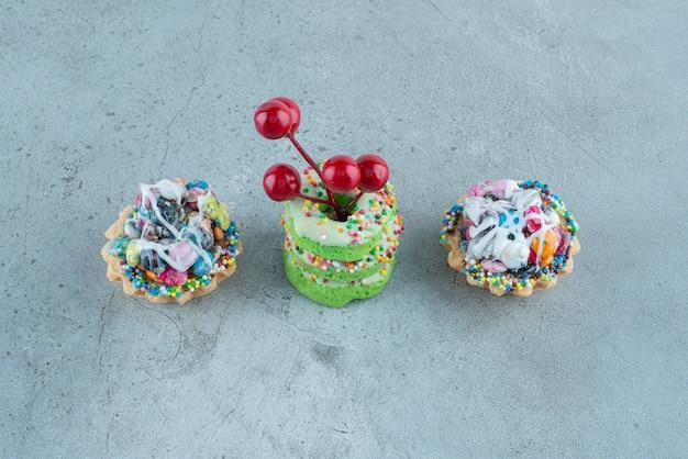 大理石の背景にキャンディカップケーキと小さなドーナツ。高品質の写真