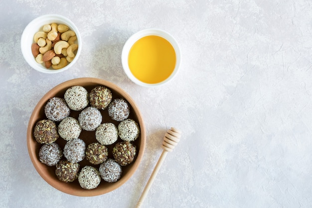 Candy energy balls with cashews, hazelnuts, peanut butter, almond and honey in the clay bowl top view with copy space on the light background.