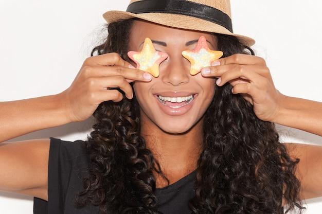 사탕 눈. 펑키 모자를 쓴 장난기 많은 젊은 아프리카 여성이 눈 앞에 사탕을 들고 흰색 배경에 서서 웃고 있습니다.