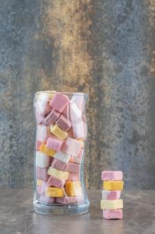 Баночка для конфет, полная желейных конфет. вертикальное фото.