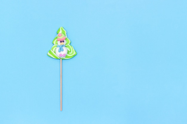 Candy lollipop of funny snowman and christmas tree on blue background.