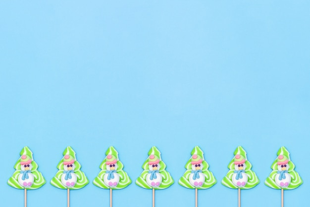 Candy lollipops of funny snowmans and christmas tree on blue background.