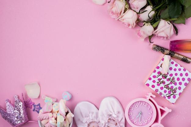 ピンクの背景の女の子のためのキャンディマシュマロとサテンのスリッパ。自転車の形をした時計
