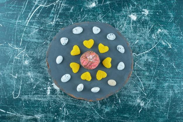 青のボード上のチョコレートでコーティングされたクッキーの周りのキャンディーロックとマーマレード。