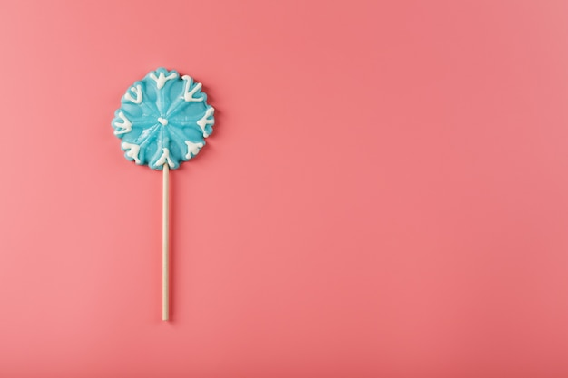 Candy in the shape of a blue snowflake on a pink background. minimalistic flat composition, free space.
