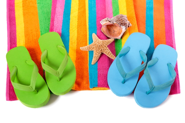 Пляжное полотенце полосы конфеты с шлепки, морские звезды и раковины, изолированные на белом.