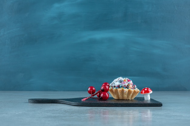 Candy topped cupcake and christmas ornaments on a black board on marble surface