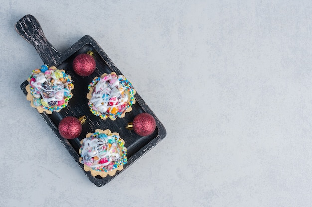 Candy topped cupcakes and baubles in a black tray on marble surface