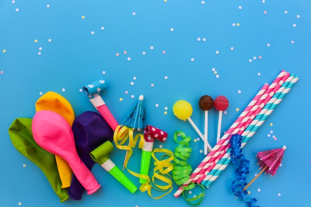 Candy, whistles, streamers, balloons on holiday table.