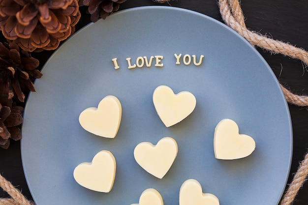 Candy white chocolate in heart, i love writing on a blue plate with cones