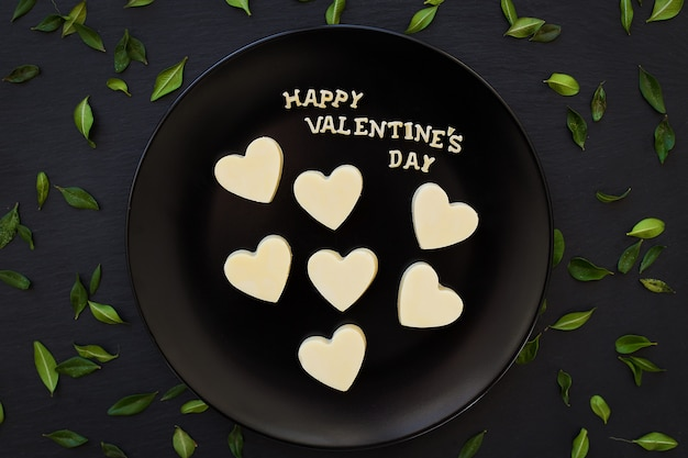 Candy white chocolate heart-shaped inscription happy valentine on a black plate with green leaves