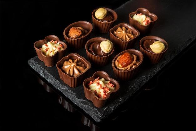 スレートボードにクリームとナッツのキャンディー黒の孤立した背景にチョコレートの盛り合わせレストランのデザートのアイデア