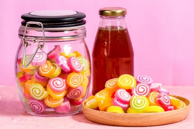 ピンクの背景のテーブルの上の瓶に蜂蜜とお菓子します。