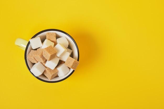 Кубики тростникового коричневого и белого сахара в желтой чашке на желтой поверхности, вид сверху