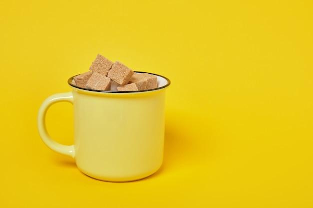 Кубики тростникового коричневого сахара в желтой чашке на желтой поверхности копией пространства