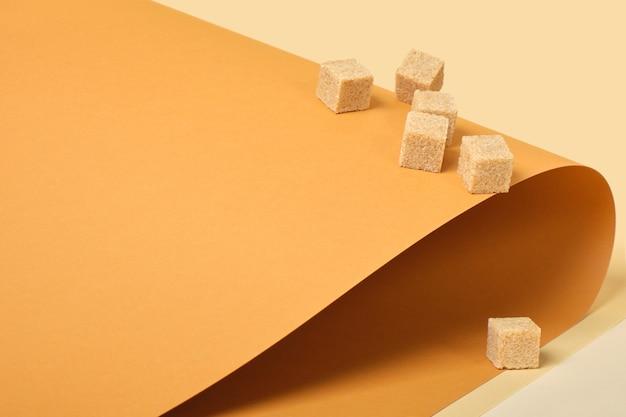 Кубики тростникового сахара на коричневом фоне, копия места цвета тенденции, рулонная бумага, бежевый фон