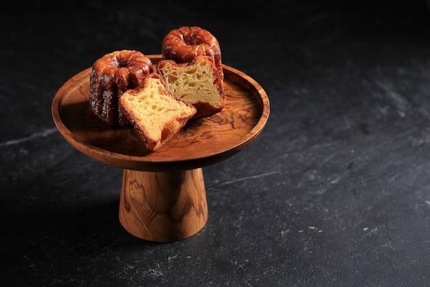 Классические французские кондитерские изделия canele бордо на деревянной подставке для торта, изолированной на черном мраморном фоне. скопируйте место для текста, рецепта, рекламы
