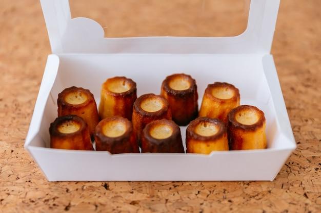 Свежеиспеченные canelés внутри белой коробки.
