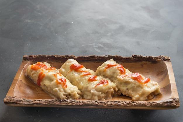 Canelones (каннеллони) с мясной пастой и сыром и помидорами на тарелке