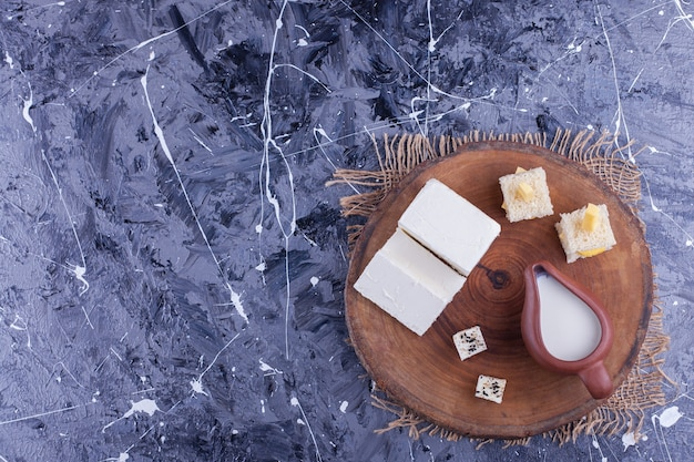 Canepes, sliced cheese and fresh milk on wood piece.