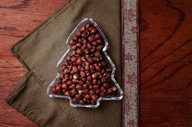 헤이즐넛이 가득한 크리스마스 트리 모양의 용기. 평면도. 공간을 복사합니다.