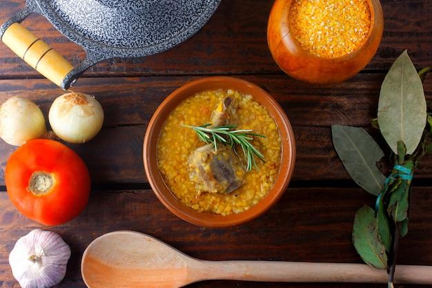 Canjiquinhaは、豚カルビと砕いたトウモロコシを使ったブラジル料理の伝統的な料理で、素朴な木製のテーブルのセラミックボウルに入れられます。クローズアップビュー