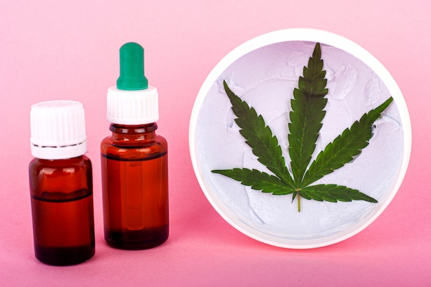 Cannabis-based cosmetic oils, bottles with marijuana extract and organic hand and face cream for skin restoration.